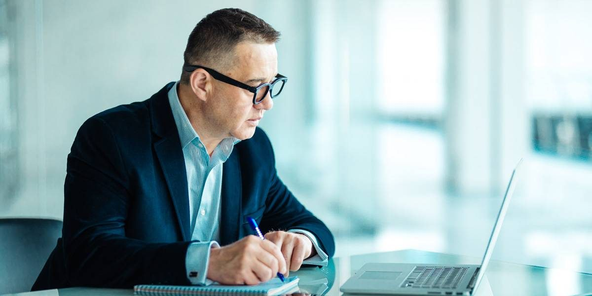 Male with blue suite on sitting at table taking notes from his laptop.