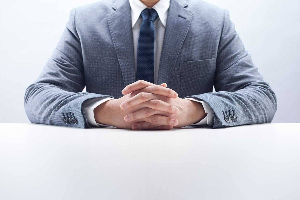 Man wearing grey suite with hands clasped