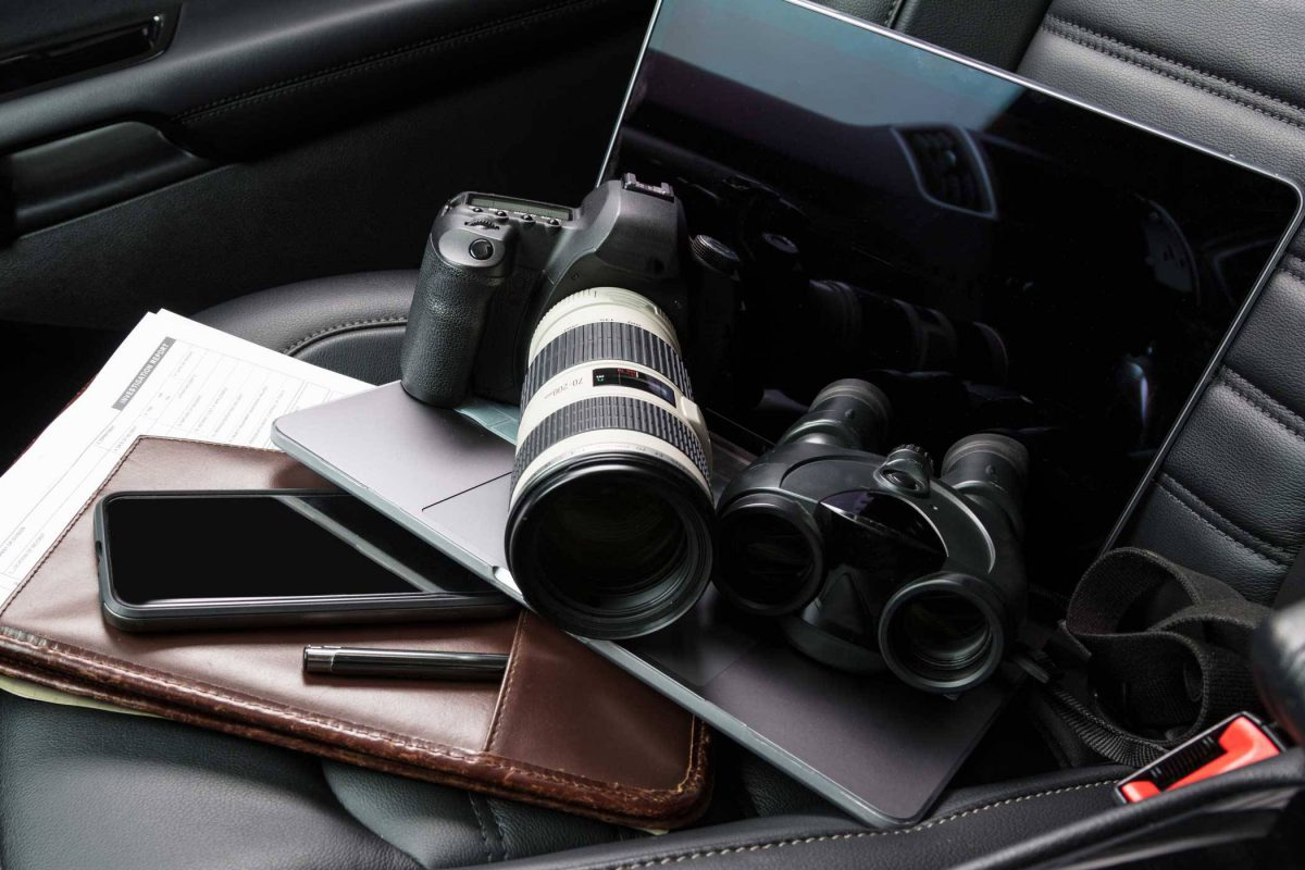 camera and binoculars sitting on the from seat of a vehicle