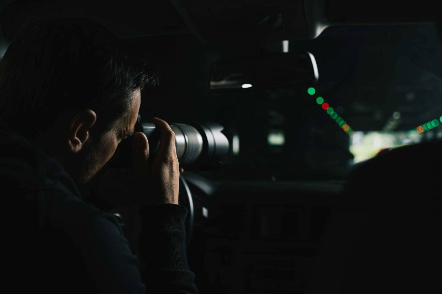 male sitting in a vehicle at night taking mysterious photos