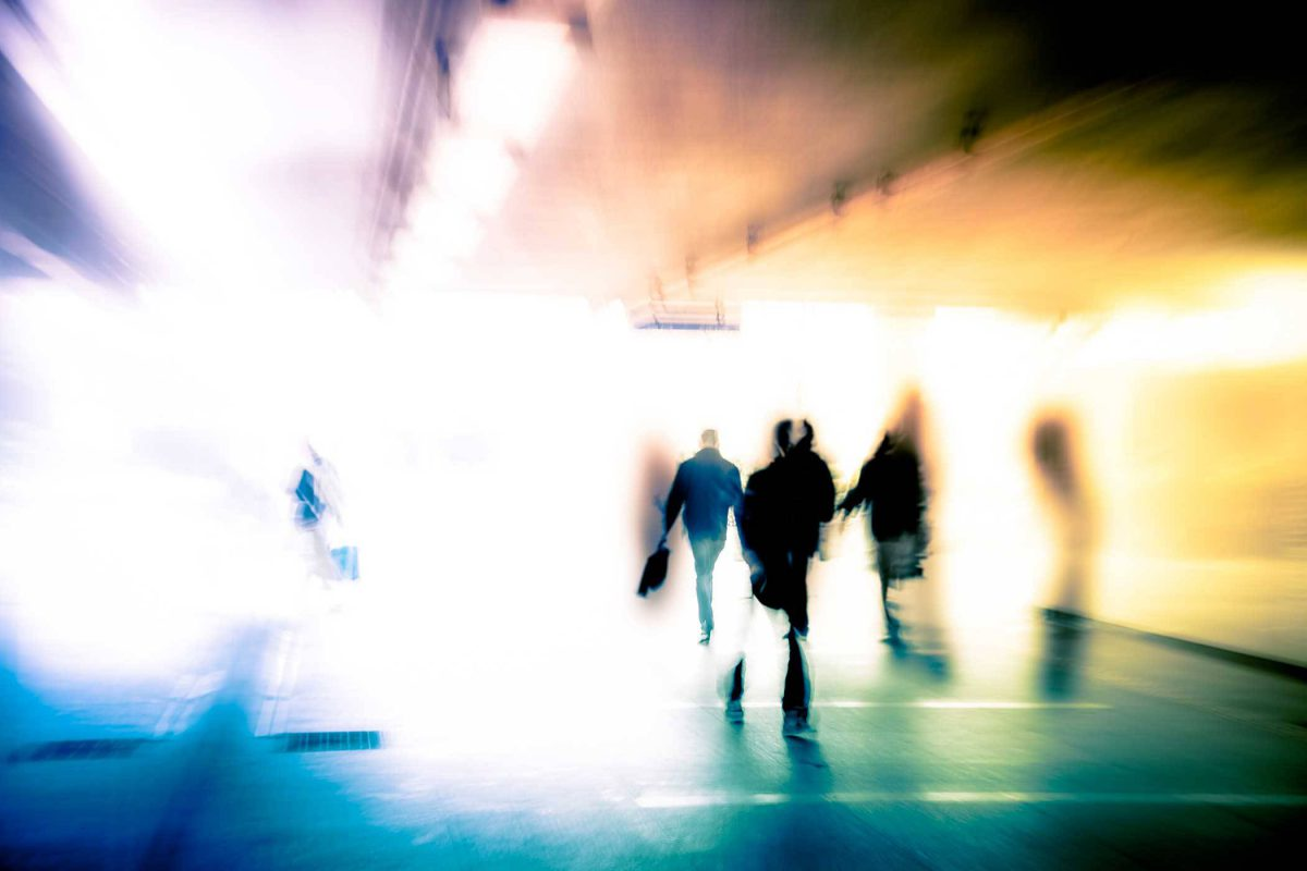 blurred image with people walking and bright light radiating through